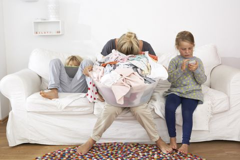 Exhausted mother with laundry basket on couch with children using digital tablet and cell phone
