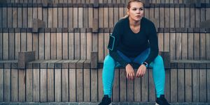 Exhausted sportswoman resting on a bench