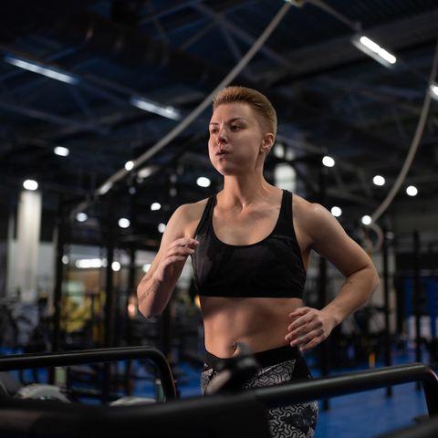 exhausted sportswoman running on treadmill
