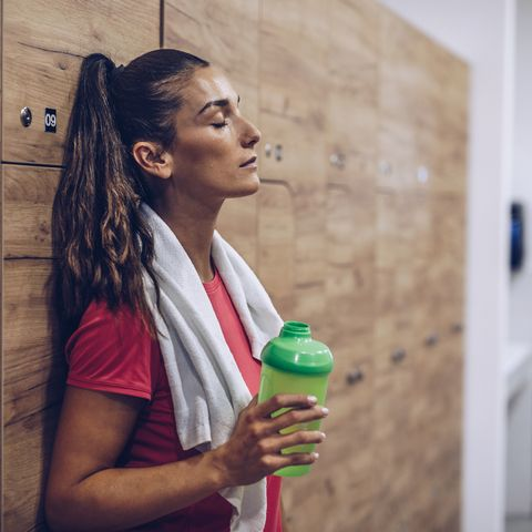 Exhausted woman in locker room after sports training.