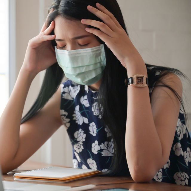 exhausted woman wearing mask using laptop at home