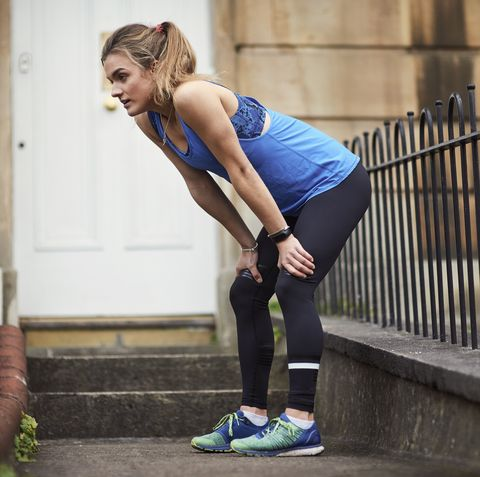 Exhausted young female runner outside front door