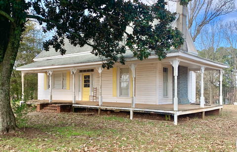 a white farmhouse with yellow shutters that's available for free if you're willing to move it off the lot