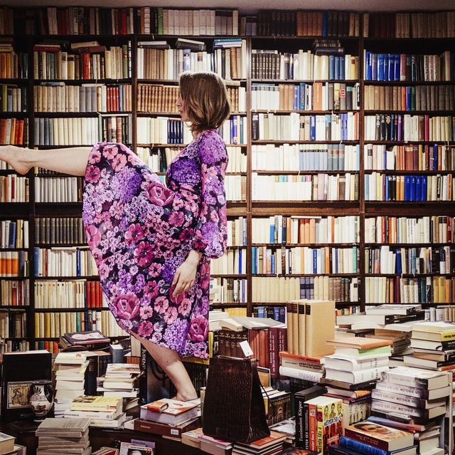 exuberant woman dancing on book stacks in library
