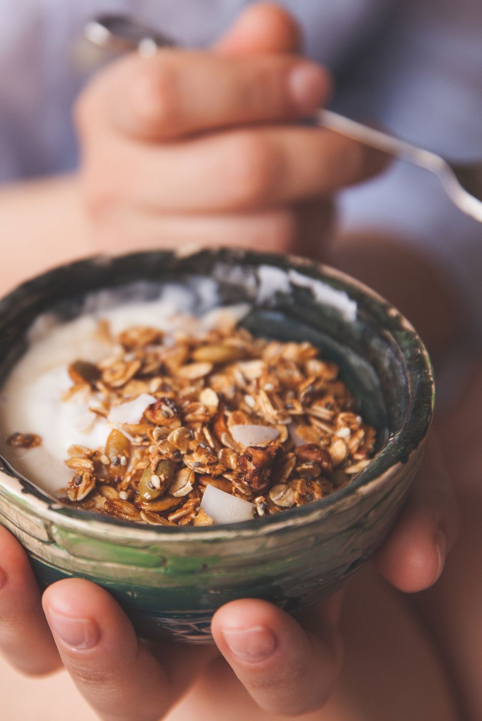 Young woman with muesli bowl. Girl eating breakfast cereals with nuts, pumpkin seeds, oats and yogurt in bowl. Girl holding homemade granola. Healthy snack or breakfst in the morning.