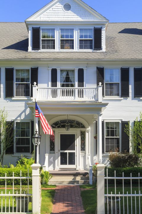facade of home with white picket fence and flag