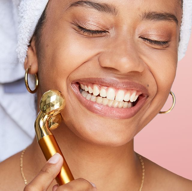 woman rolling face with gold massager