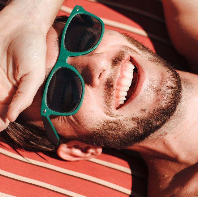 man with green sunglasses sunbathing