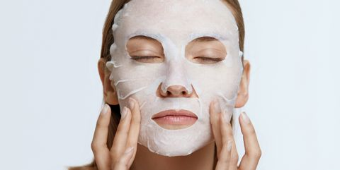 facial mask woman using sheet mask on face skin for spa care