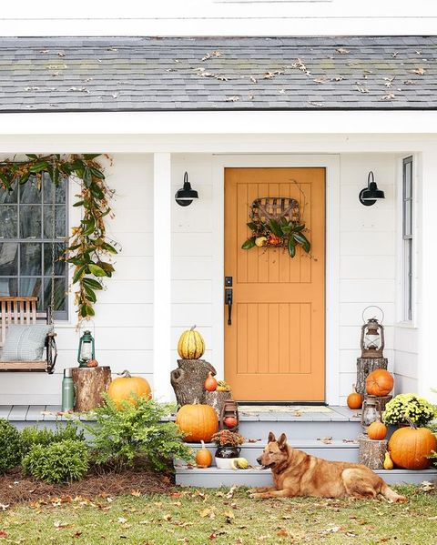 a white cottage with an orange door with a wreath and stacks of pumpkins and mums