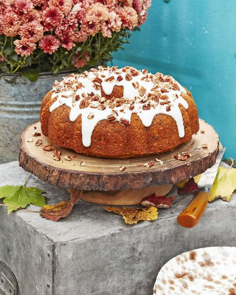 a round bundt cake made using pumpkin with white cream cheese icing and pecans on top