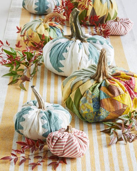 fabric pumpkins line the center of a fall table
