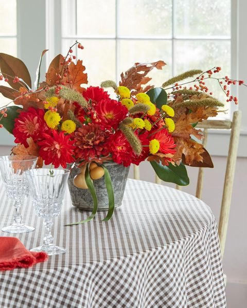 bold red and yellow blooms in a galvanized vase accented with fall leaves and berries