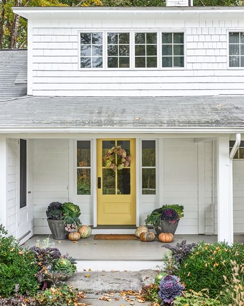 fall cabbages tucked into the landscaping and planters with patina are a nice change from the season's ever popular mums and a wreath of dried flowers hung on the happy gold door and pumpkins scattered casually below makes for an effortless fall look