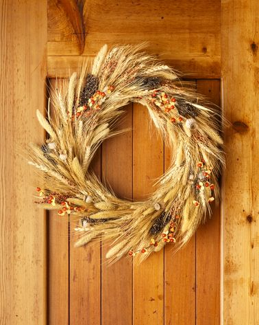 a wheat wreath hangs on a honey colored wooden door