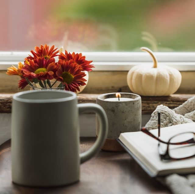 fall reading nook with blanket candle mug and white pumpkin