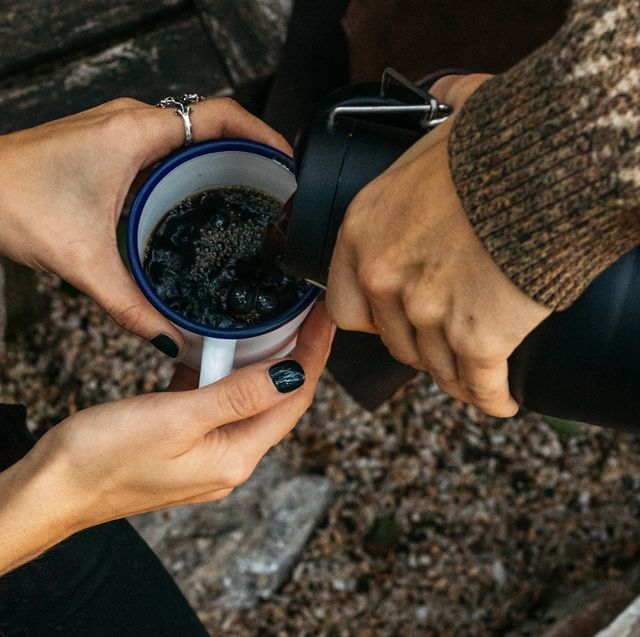 coffee being poured into a camping mug from a thermos