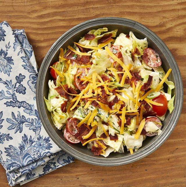 ranch salad with shredded cheddar in black bowl