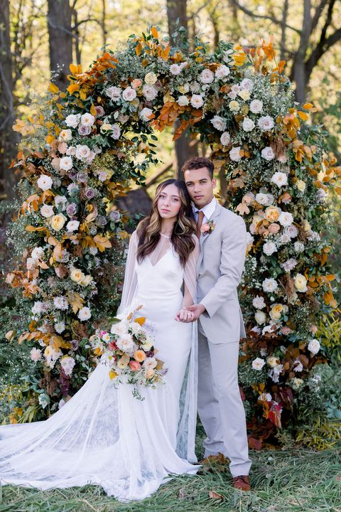 couple poses at a fall wedding ceremony arch