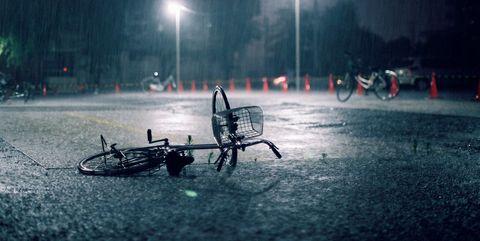 Fallen bicycle in heavy rain.