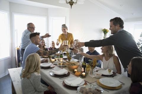 Family and friends toasting champagne and wine glasses at Thanksgiving dinner table