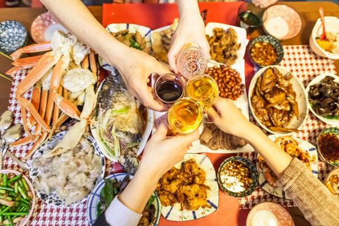 family are toasting beers and wines over chinese traditional dishes celebrating for chinese new year, tokyo, japan
