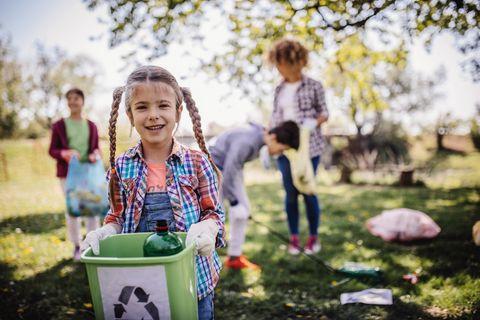 en primer plano, una niña con un cubo de basura limpiando el bosque
