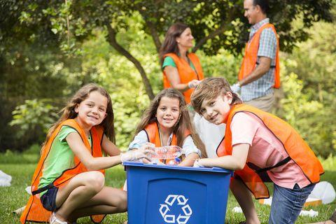un grupo de niños, con sus padres detrás, limpia de residuos el bosque