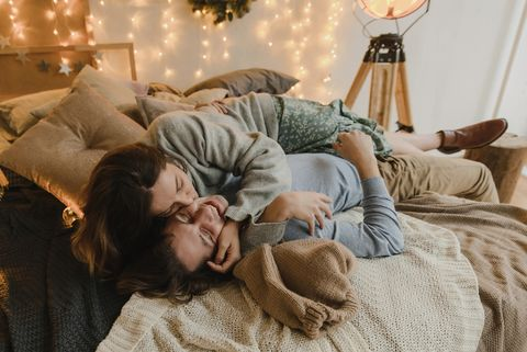 family couple lying on bed at christmas