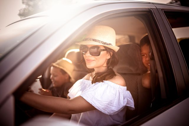 family driving in  car on countryside road trip