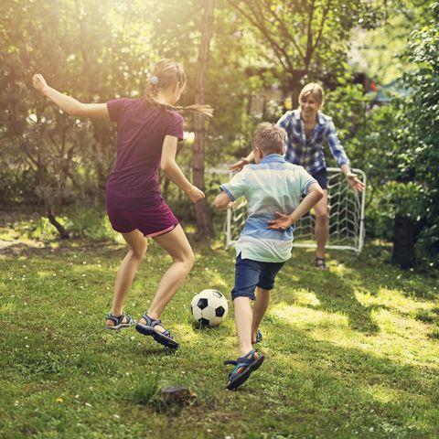 family having fun playing soccer in the garden