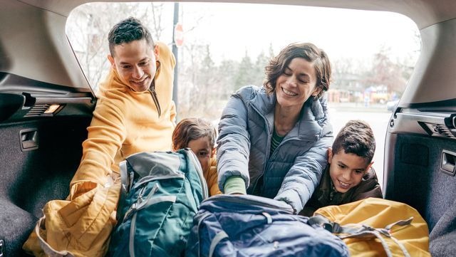 family loading  a car trunk before the road trip