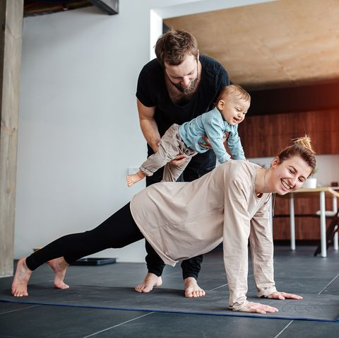 family morning exercise mother doing plank, father holding baby on her back