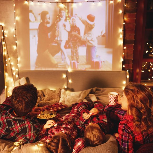 family mother father and children watching projector, film, movi