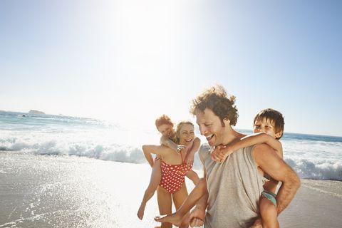 unos padres juegan en la playa con sus hijos