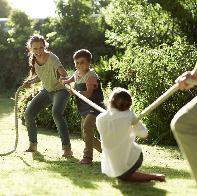 family playing tug of war in park