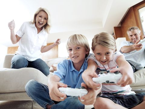 Family playing with video games console at home, smiling, front view, low angle view
