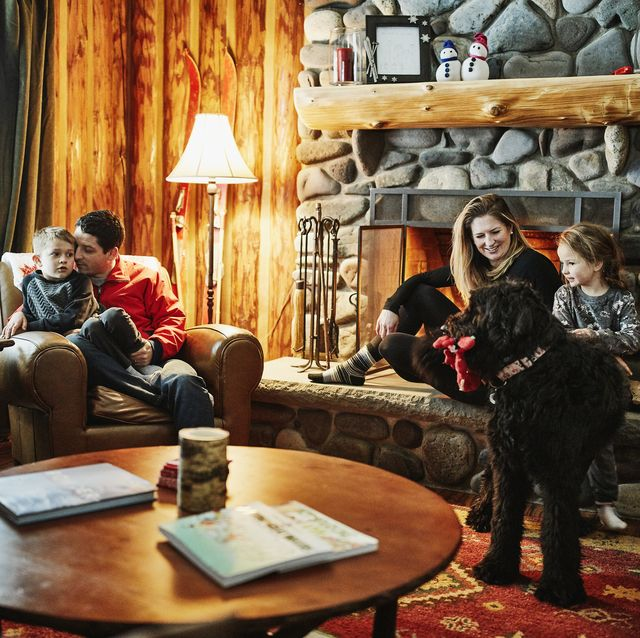 family sitting by fireplace in winter cabin