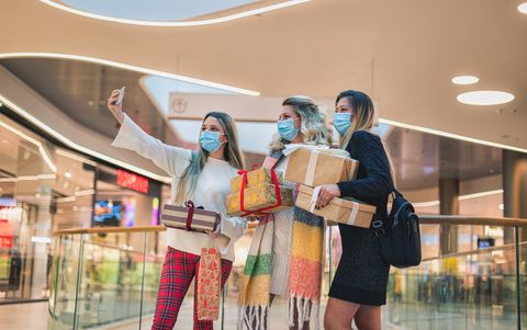 family taking selfie while enjoying christmas shopping at the mall during the covid 19 pandemic they wears a protective mask to protect from coronavirus covid 19