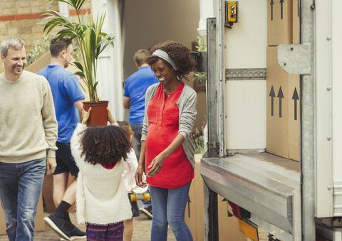 Family unloading moving van outside new house