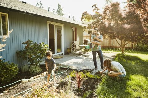 family watering garden in backyard on summer morning
