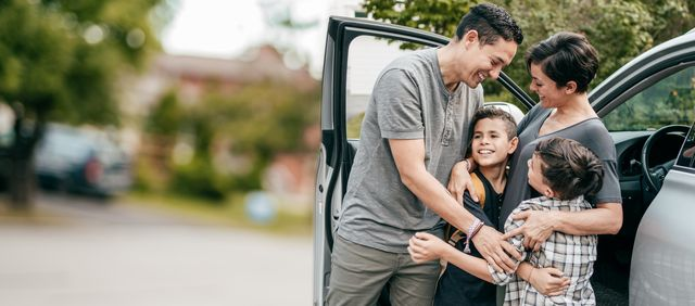 family with two kids  moment with hugs near car