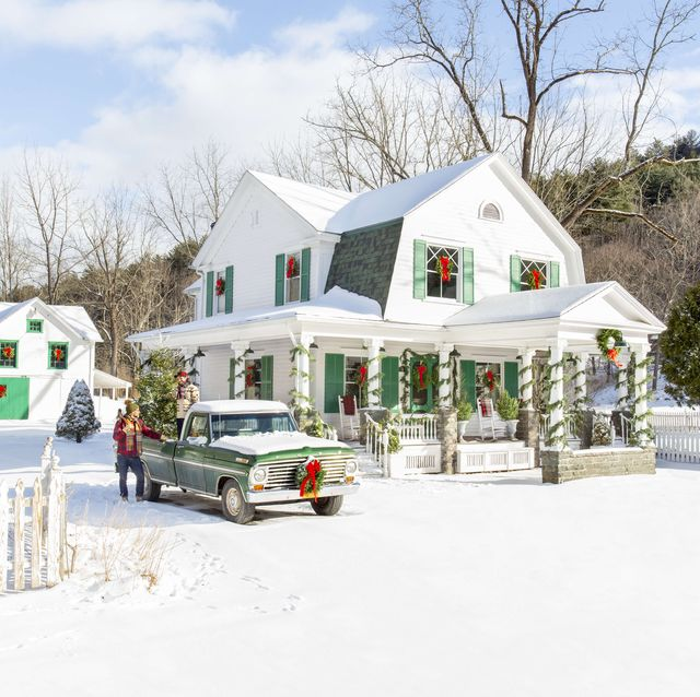 white farmhouse with green shutters and holiday decor