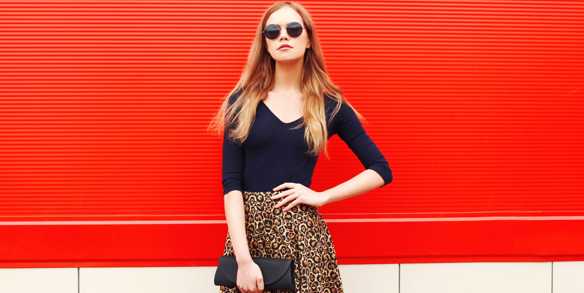 Fashion beautiful woman in leopard skirt sunglasses handbag clutch posing