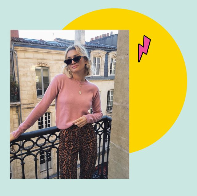 french fashion icon anne laure mais stands on a balcony in paris wearing a pink jumper, leopard trousers and black sunglasses
