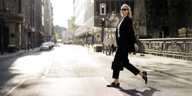 fashionable businesswoman crossing street in city
