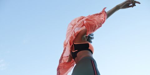 Fashionable woman wearing jacket with sports clothing against clear sky