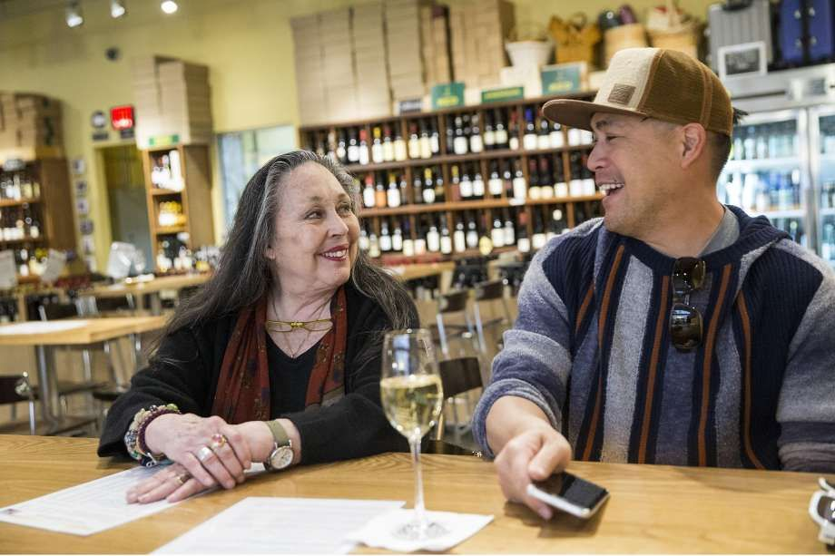 Jeanne Rose has a glass of champagne at Ferry Plaza Wine Merchant with her friend Jeff Chan (right) after shopping at the Ferry Plaza Farmers Market.