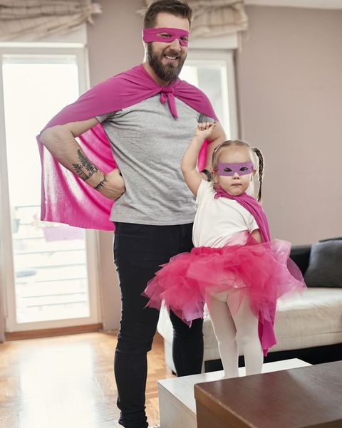 father and daughter playing superhero and superwoman
