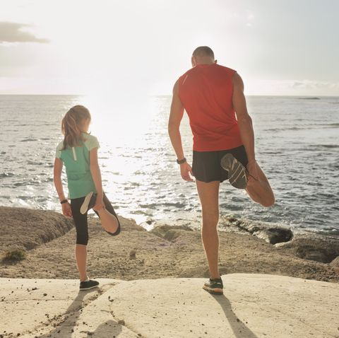 father and daughter stretching during jogging